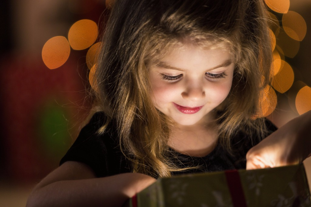 curious-girl-peeks-inside-a-christmas-present-picture-id580120952